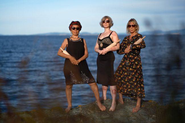 Tre kvinner står ved havet.