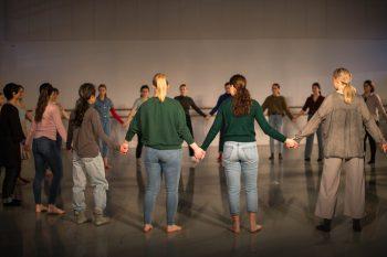16 dansere står i en stor ring og holder hverandre i hendene