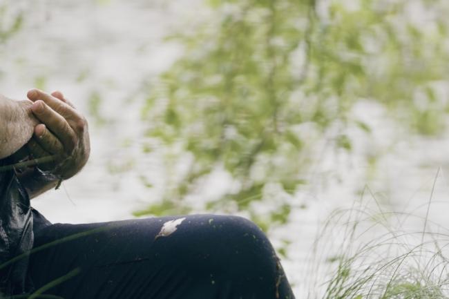 Bilde av en amnn som sitter i skogen ved et vann